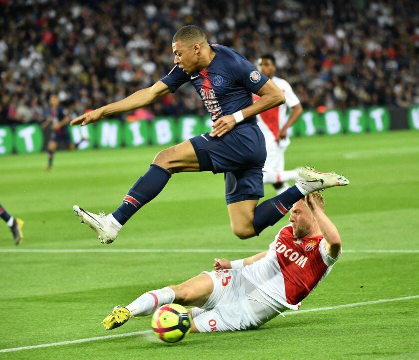 Kamil Glik z Monaco walczy o piłką z Kylianem Mbappe z PSG